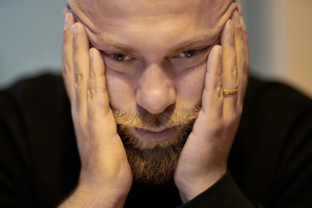 close up of a man with his hands on his cheeks, expressing negative emotions